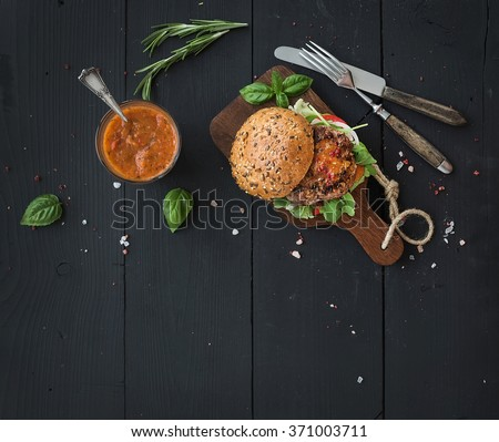 Fresh homemade burger on dark serving board with spicy tomato sauce, sea salt and herbs over dark wooden background. Top view, copy space, horizontal