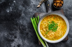 Fresh homemade chicken soup with noodle at table. Black background. Top view. Copy space