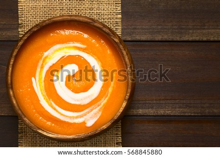 Fresh homemade cream of carrot soup with a swirl of cream on top served in wooden bowl, photographed overhead on dark wood with natural light (Selective Focus, Focus on the soup)