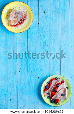 Fresh homemade crepes served on a plate with strawberries and blueberries, on a light blue wooden background, free space for text. Top view #1014289639