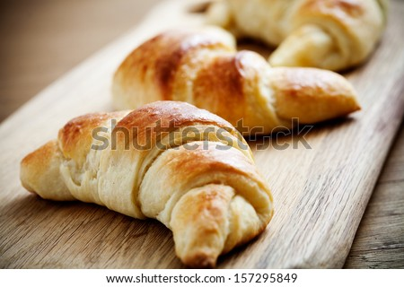 Fresh homemade croissants on wooden table, selective focus
