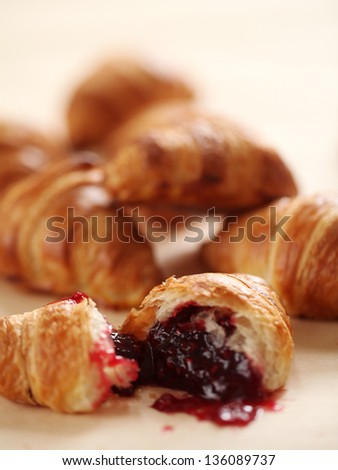 Fresh homemade french croissants with strawberry jam on a linen tablecloth