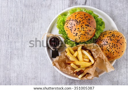 Fresh homemade hamburger with black sesame seeds in white plate with fried potatoes, served with ketchup sauce in glass jar over gray wooden surface. Top view