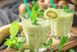 Fresh homemade kiwi smoothies with banana, milk, mint and honey. Healthy organic drink. On a wooden table with ingredients. Close up and selective focus