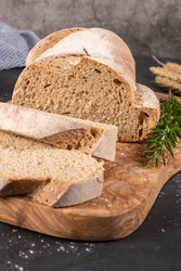Fresh homemade leavened bread in the sun, partially sliced. Bread is located on a wooden surface. Hobbies, baking rye bread at sourdough at home. Healthy food concept, traditional craft bread. Closeup