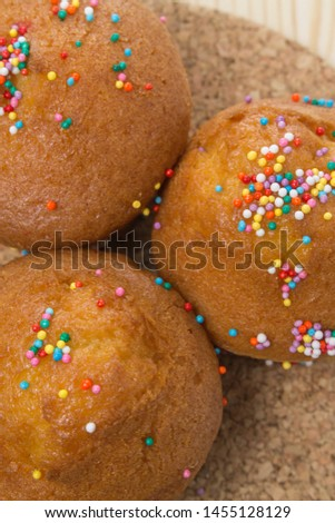 Fresh homemade muffins in color sprinkle, vertical closeup. Cake dessert sweet pastry