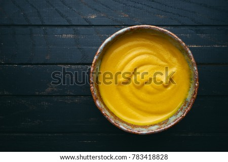 Fresh homemade organic mustard in bowl on wooden background top view #783418828