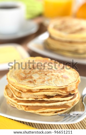 Fresh homemade pancakes with coffee, orange juice and butter in the back (Selective Focus, Focus on the front of the upper three pancakes)