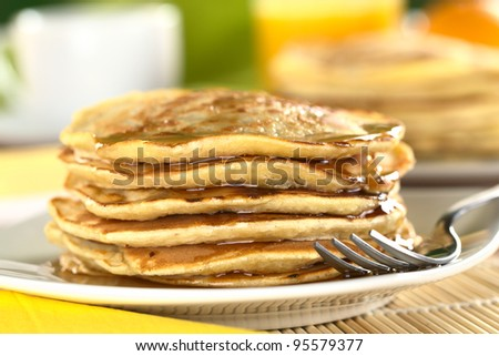 Fresh homemade pancakes with maple syrup (Selective Focus, Focus on the front of the pancakes)