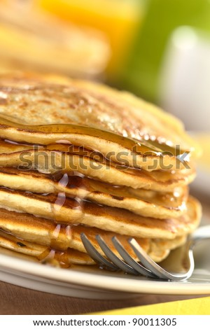 Fresh homemade pancakes with maple syrup (Selective Focus, Focus on the syrup drop running down)