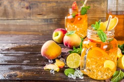 Fresh Homemade Peach Sweet Tea with Mint and Lemon Slices, Summer cold fruit drink. Wooden background with fresh peach, copy space