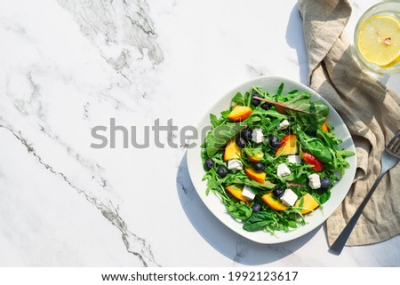 Fresh homemade salad with nectarines, blueberries, arugula, spinach and feta cheese on white marble background with hard shadows. Healthy vegetarian food. Top view. Space for text. Сток-фото ©