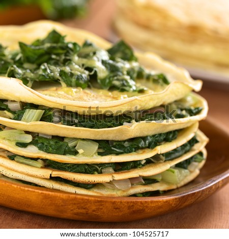 Fresh homemade savory crepes layered with chard (mangold) and onion with cheese on top served on wooden plate (Selective Focus, Focus on the front of the filling and the upper crepe)