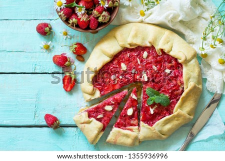 Fresh homemade strawberries galette with nut cream on kitchen table. Top view flat lay background with copy space. Copy space.