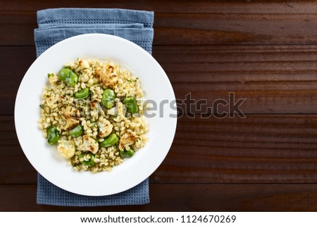 Fresh homemade vegan salad made of pearled barley, broad beans, roasted cauliflower and parsley, photographed overhead with copy space
