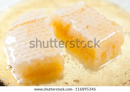 Fresh honey and two honeycomb slices on a plate