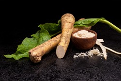 Fresh Horseradish Roots and spicy sauce in wooden bowl on dark background.