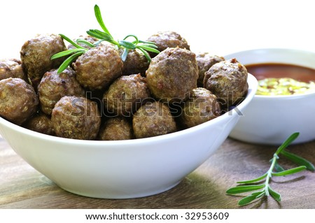 Fresh hot meatball appetizers served in white bowl with dipping sauce - stock photo