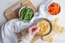 Fresh hummus dip with pea pods, carrots and tortilla chips