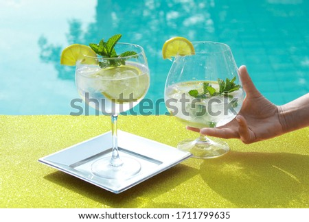 Photo of Fresh image of drinks in glass with ice and lemon in swimming pool summer scene