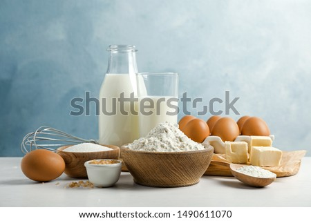 Fresh ingredients for delicious homemade cake on white wooden table against blue background
