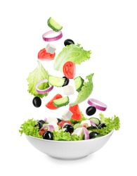 Fresh ingredients for Greek salad falling into bowl on white background