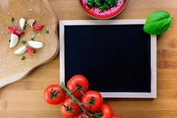 Fresh Ingredients on wooden board for cooking garlic, tomato, basil dishes. Board for the inscription. Free copy space, top view