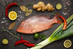 Fresh ingredients to cook fish, red snapper, leak, lime, lemon, parsley, chili pepper, ginger. Top view