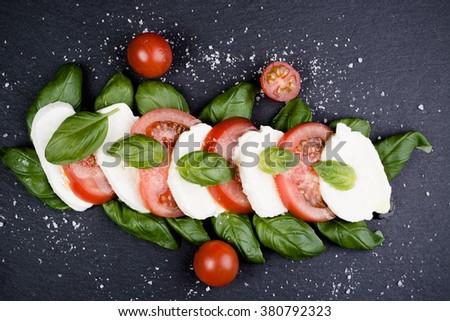 Fresh italian caprese salad with mozzarella and tomatoes on dark plate Stok fotoğraf ©