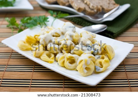 fresh italian pasta tortellini with blue cheese sauce on white platter