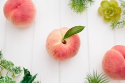Fresh Japan White Peaches and Green Leaves on Wooden White Background