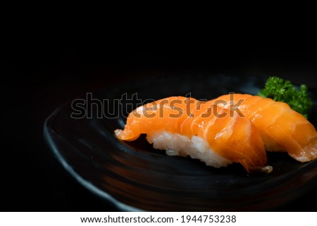 Fresh Japanese sushi salmon served with wasabi in Japanese restaurant. Eating Japanese food such as salmon sushi and sashimi is healthy and tasty. Salmon sushi and Japanese food concept. Copy space.