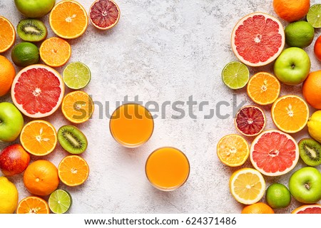 Fresh juice vitamin c drink in citrus fruits background flat lay, healthy lifestyle vegetarian organic antioxidant detox diet beverage. Tropical summer assortment grapefruit, orange, apple #624371486