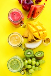 Fresh juices smoothie red green yellow Tropical fruits water melon strawberry apple kiwi mango banana pine apple pomegranate grape on yellow background. Selective focus bottles. Base colors. Top view