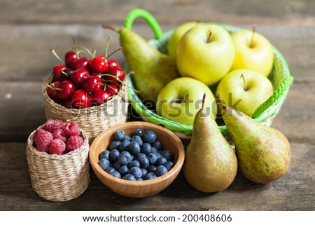 Fresh juicy apples, pears and berries on a wooden table