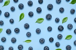 Fresh juicy blueberries with green leaves on blue background. Blueberries background. Flat lay top view copy space. Healthy berry, organic food, antioxidant, vitamin, blue food. Blueberry pattern