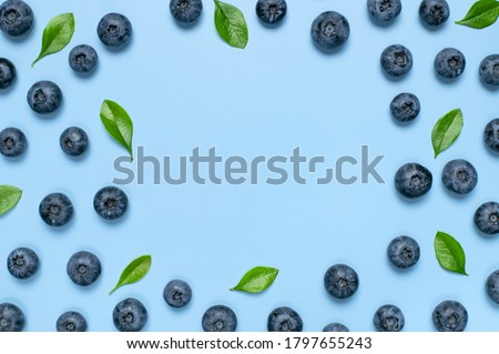 Fresh juicy blueberries with green leaves on blue background. Blueberries background. Flat lay top view copy space. Healthy berry, organic food, antioxidant, vitamin, blue food. Blueberry frame