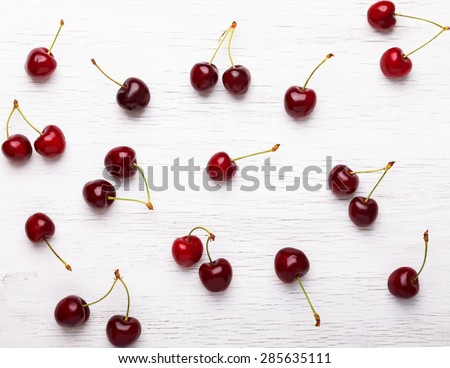 Fresh juicy cherries on the white wooden background, top view