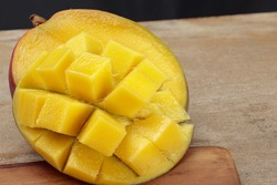 Fresh juicy cutting mango on a wooden table. Shallow depth of field