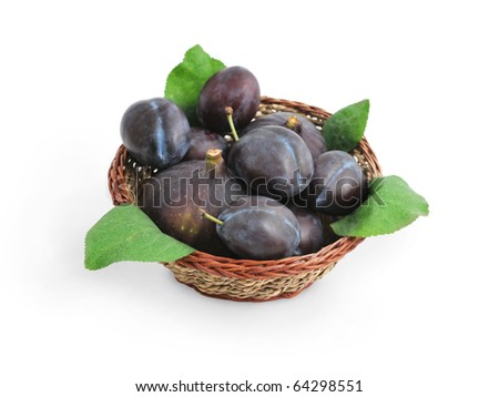 Fresh juicy fruits, plums and figs, with green leaves in a basket isolated on white background