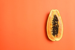 Fresh juicy halved papaya on coral background, top view. Space for text
