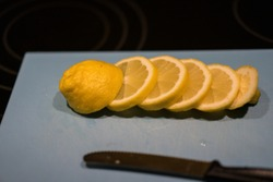 Fresh juicy lemon. Slice thin slices on a cutting board