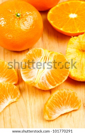 Fresh, juicy mandarin oranges shown on a wood cutting board with whole orange and peeled sections