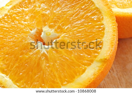 Fresh, juicy orange on wooden cutting board.  Macro with shallow dof. - stock photo