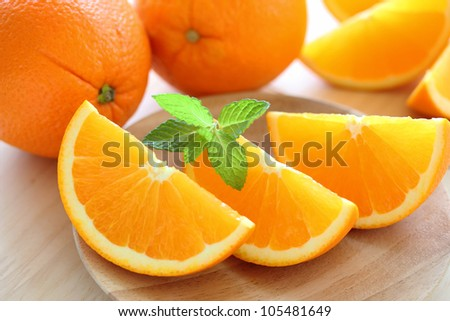 Fresh juicy oranges with mint leaves on  wooden plate