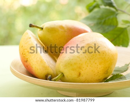 Fresh juicy pears in bowl on natural background. Selective focus