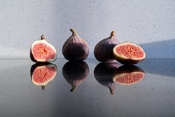 Fresh juicy Turkish Figs whole and sliced on a reflective black mirrored surface with speckled textured stone background in sunlight. Still life gourmet vegan vegetarian food.
