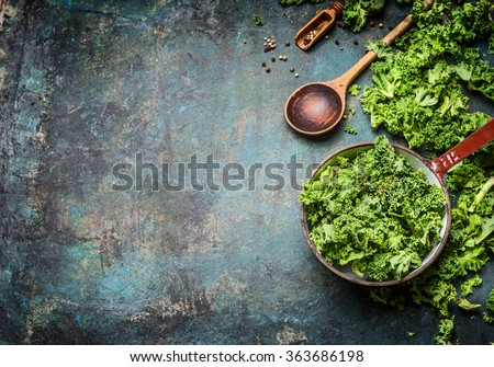 Fresh kale in cooking pot with wooden spoon on  rustic background, top view, border. Healthy food or diet nutrition concept.  Photo stock ©
