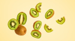 Fresh kiwi fruit flying in air on yellow. Fruity green color diet food. Summer whole, cut kiwi background. Colorful levitation concept. Falling fly kiwi, fruity creative vivid design