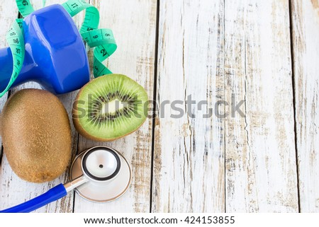 fresh kiwi,stethoscope,dumbbell and measuring tape on white wooden table background. top view